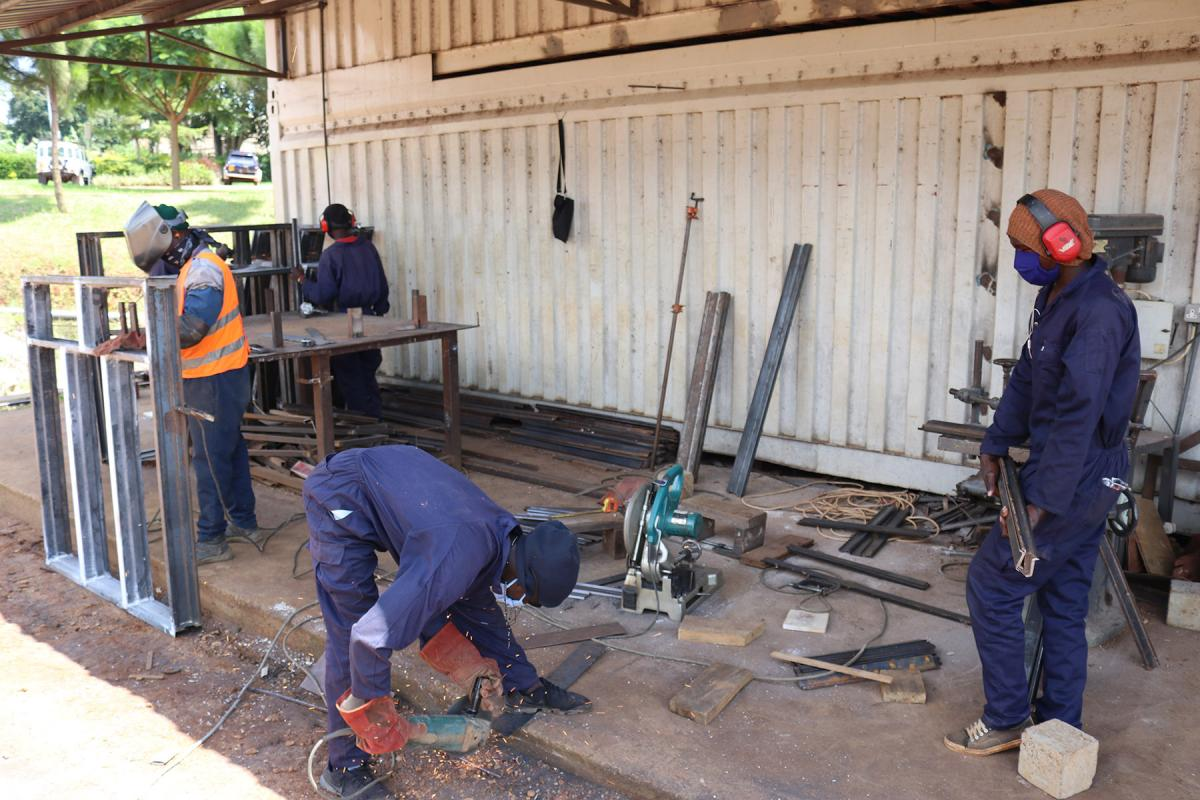 Workers trying to keep social distance during metal fabrication